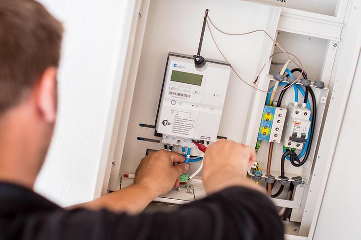 Montør setter inn automatisk strømmåler i sikringsskap.
