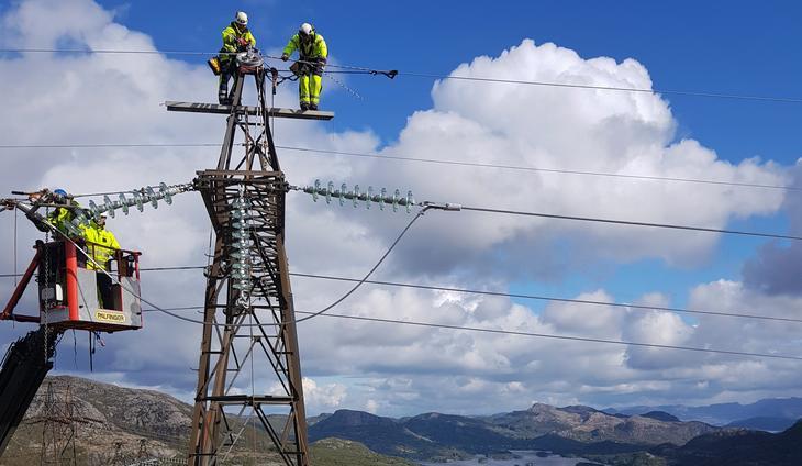 To montører står i toppen av en strømmast for å skifte anlegg, mens en annen montør står i lift og hjelper.