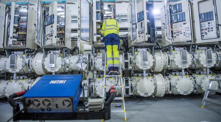 Dekslene står åpne til elektrisk anlegg på Opstad i forbindelse med idriftsettelse. En person i gule arbeidsklær står i en gardintrapp for å rekke opp til anlegget. Foto Fredrik Ringe