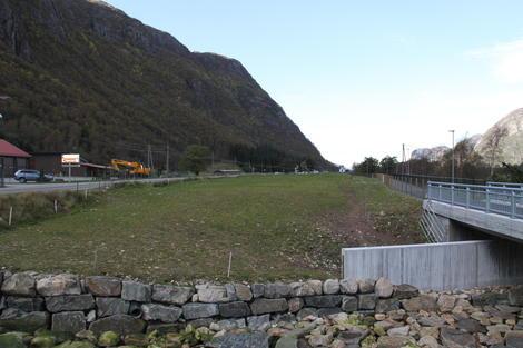 Mark langs vei og bro i Dirdal med høye fjell til venstre.