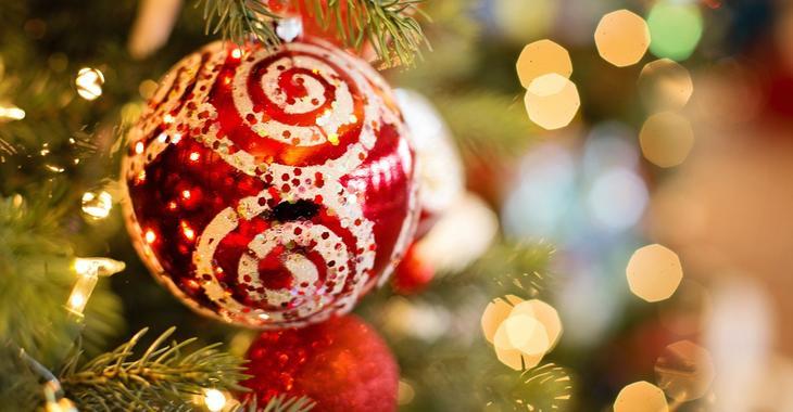 Rød julekule med hvitt mønster på juletre med lys på.