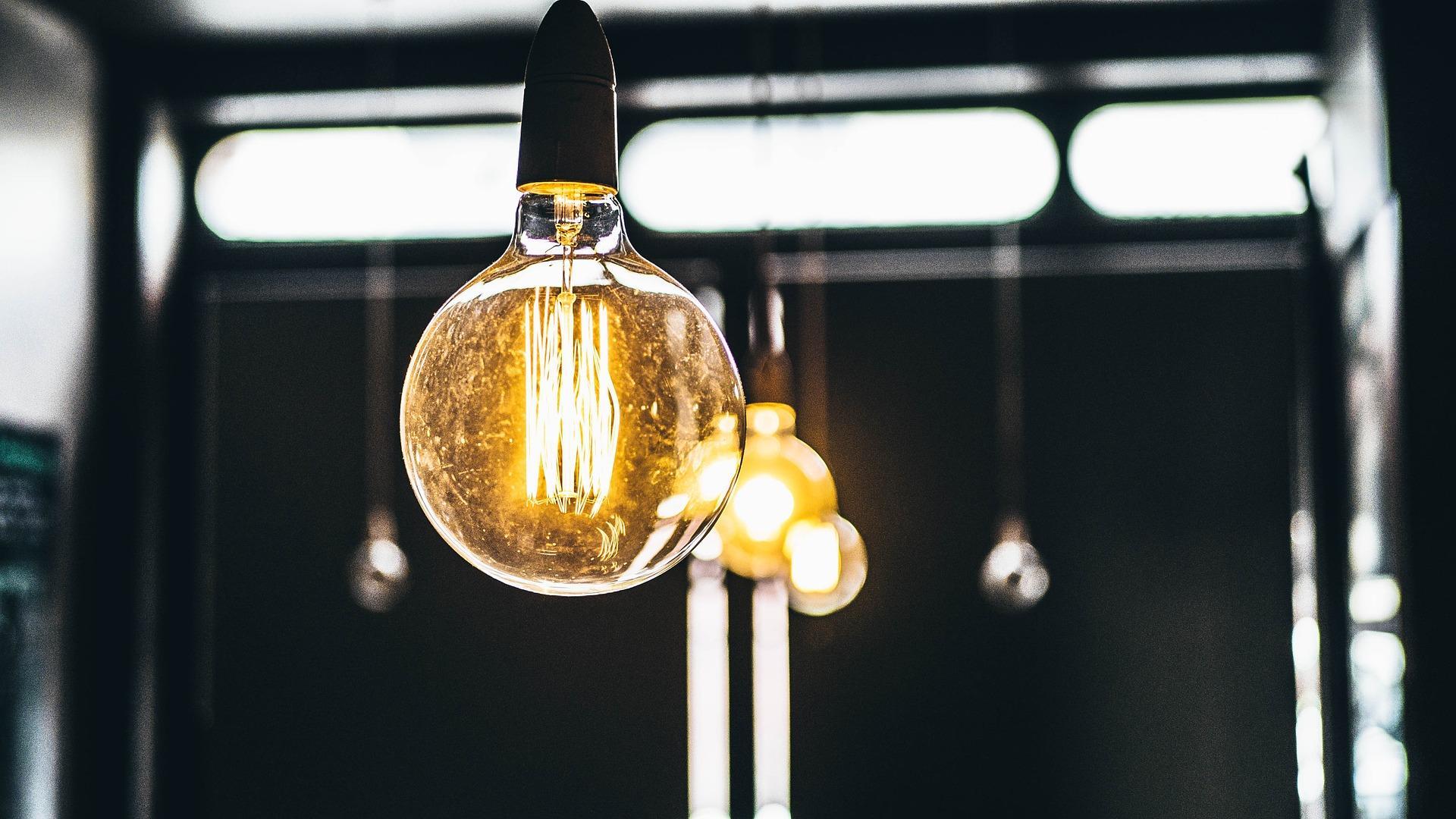 Lampe formet som en lyspære henger ned fra et tak og lyser opp rommet.