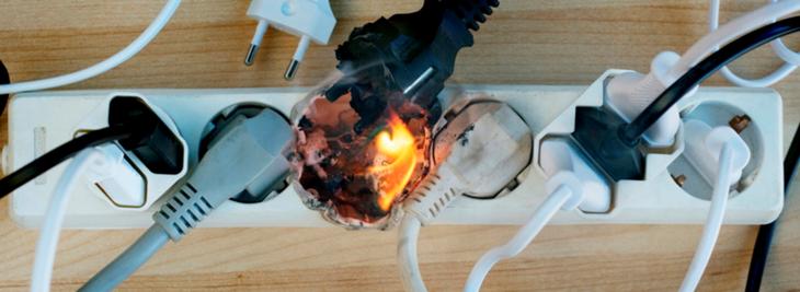 Mange ledninger er koblet til i en padde med flere stikkontakter. Flammer står opp fra en av kontaktene.