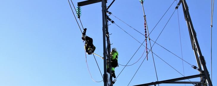 Montør ligger ute på kraftlinjen for å montere en sensorkule, mens en annen montør står i masten og hjelper.