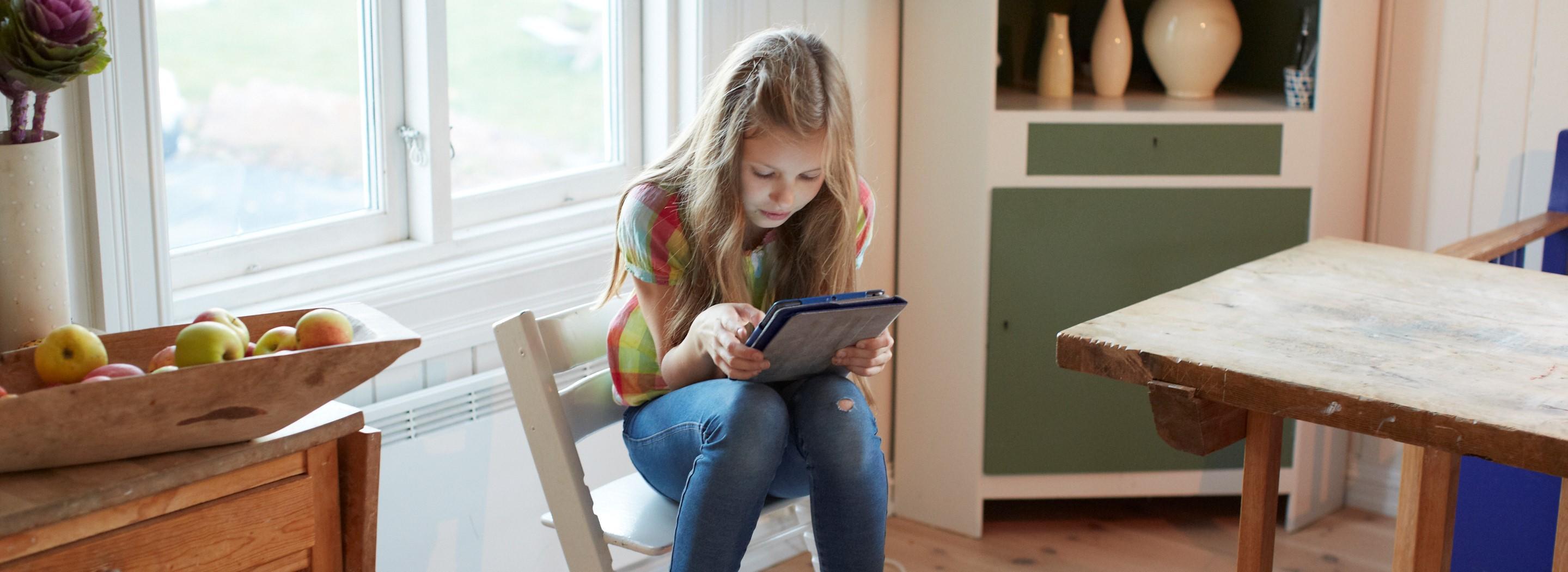 Jente sitter på en hvit kjøkkenstol med nettbrett i hendene