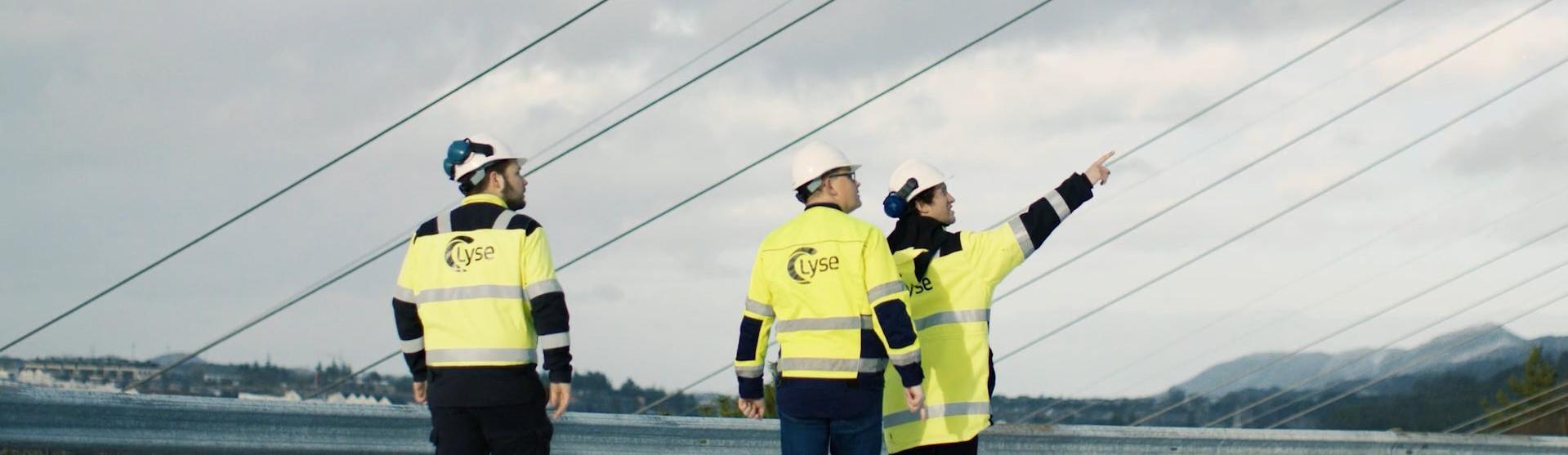 Tre ansatte i gule arbeidsjakker og hvite hjelmer er ute og ser på kraftlinjer som går over dem.