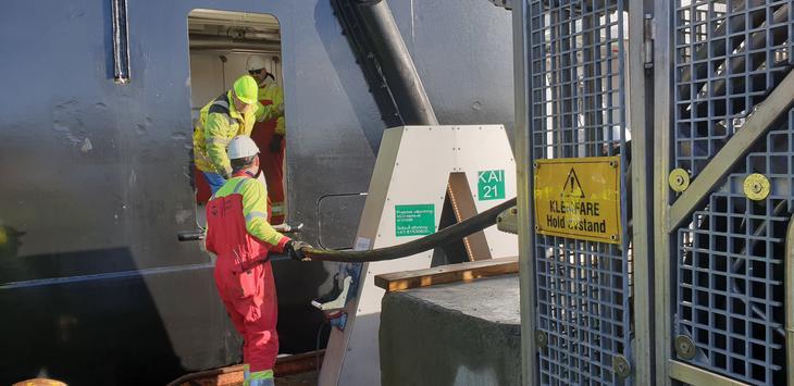 Strømkabel trekkes av ansatte mot et skip som ligger til kai.