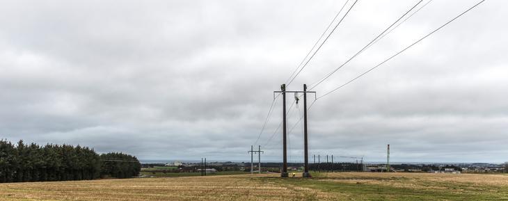Montører arbeider oppe i en ny strømmast med å koble til kraftlinjen. Foto Fredrik Ringe