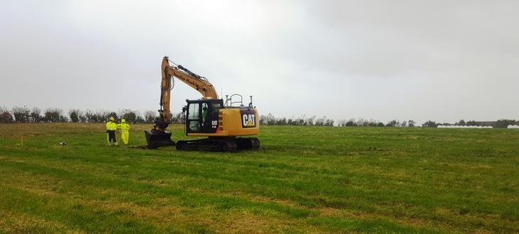Oransje gravemaskin står på grønt jorde klar til å lage sjakt