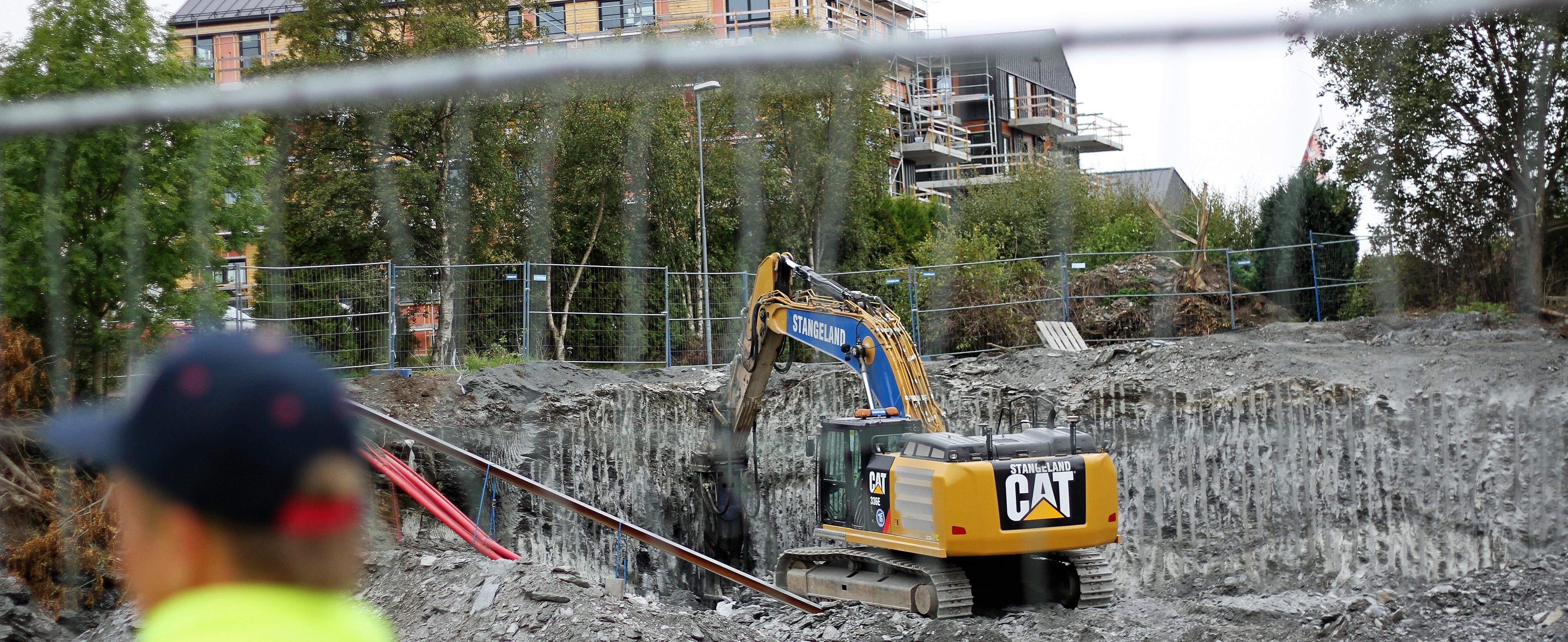 Gravemaskin står innenfor gjerder i en byggegrop