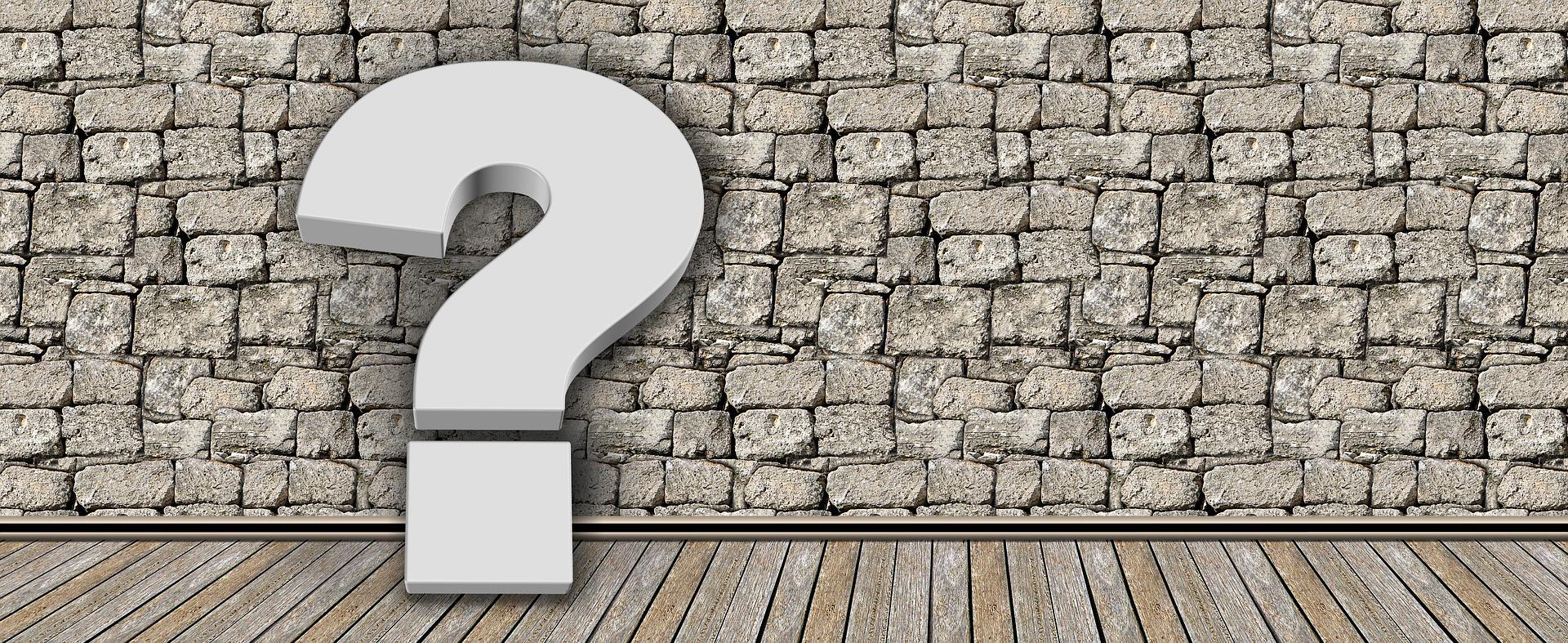 Et hvitt spørsmålstegn står opp langs en steinmur
