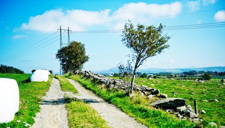 En kraftlinje går langs et steingjerde med en traktorvei på venstre siden av steingjerdet. Ved siden av veien ligger hvite høyballer.