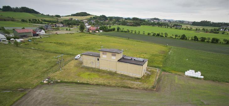 Flyfoto av Randaberg transformatorstasjon omringet av grønne marker og gårdsbygninger