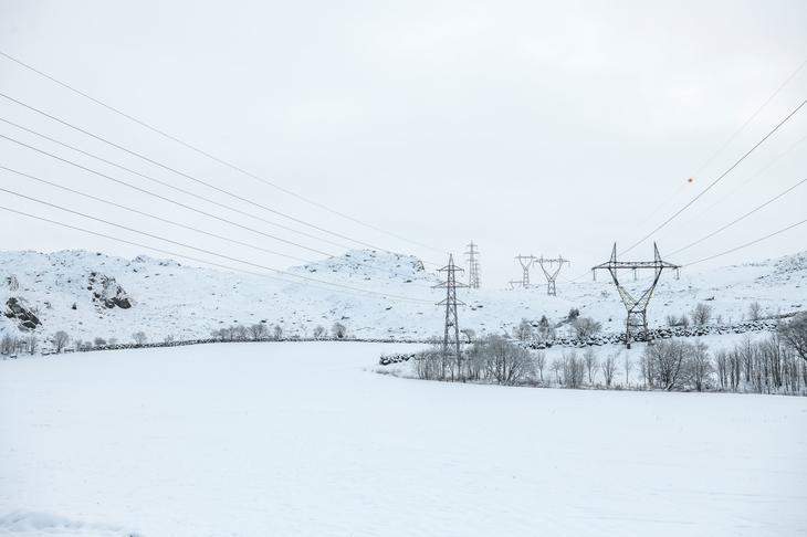 Kraftlinjer går over snøkledde marker og fjell en kald januardag. Foto Fredrik Ringe