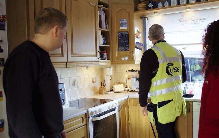 Tilsynsingeniør i DLE er hjemme på kjøkken hos kunde under et eltilsyn.