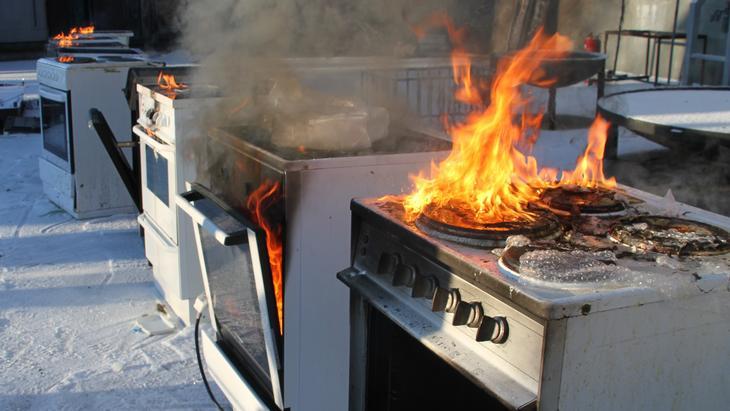 Åpne flammer fra fem komfyrer som står ved siden av hverandre utendørs etter kontrollert påtenning. Foto Brannvesenet i Sør-Rogaland