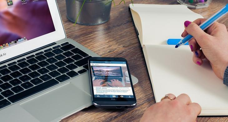 En hånd holder en tusj over en blank skriveblokk, mens åpen laptop og mobil ligger til venstre på bordet.