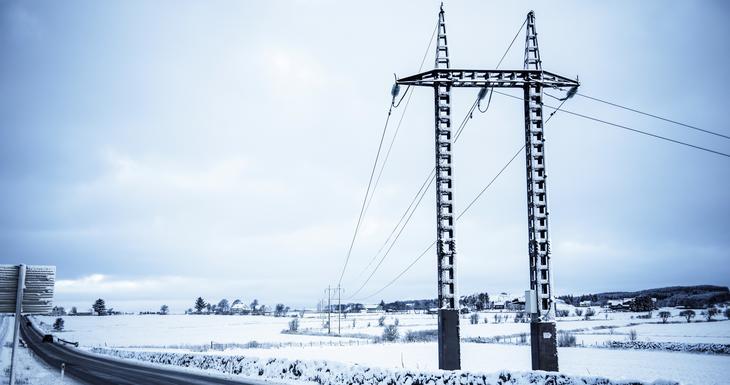 Mast og strømlinje over snødekte marker på Jæren.