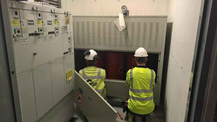 To montører i gult verneutstyr sitter på kne foran et anlegg i en nettstasjon og jobber.