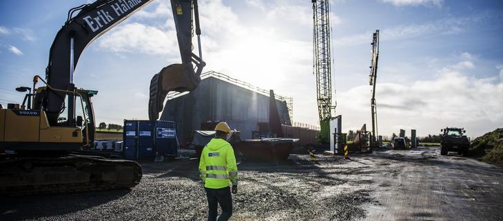 Gravemaskin står på byggeplass hvor nytt bygg er under oppføring. Foto Fredrik Ringe