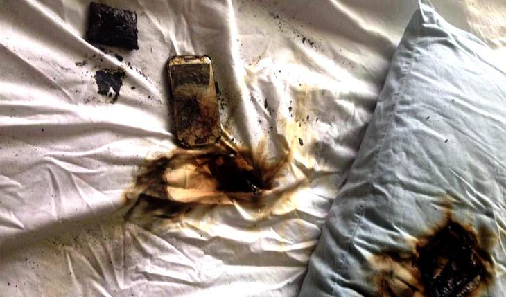 Brunsvidd mobiltelefon på hvitt laken med stort svimerke