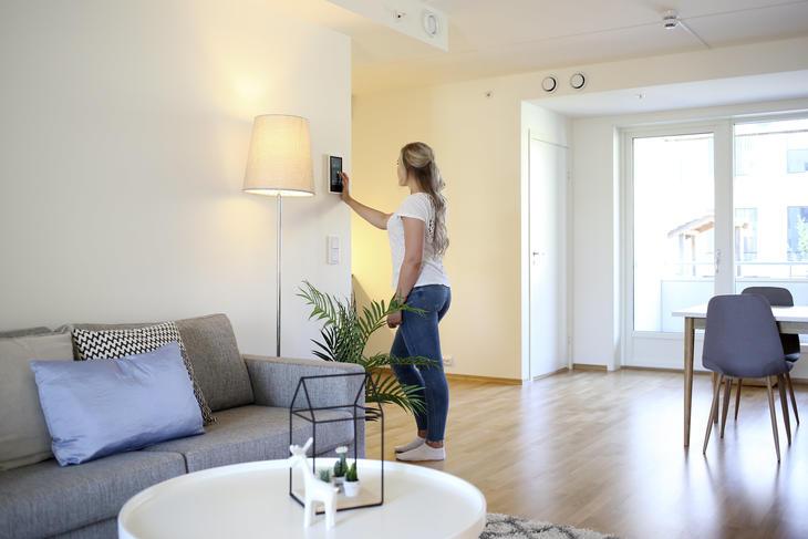 Ung kvinne står ved et styringspanel som henger på en hvit vegg i en leilighet. En stålampe og en grønn plante står på gulvet ved siden av henne og en lysegrå sofa.