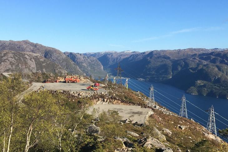 På fjellet over fjorden står strømmastene til et fjordspenn. Like ved er det laget riggplass for bygging av ny kraftlinje.