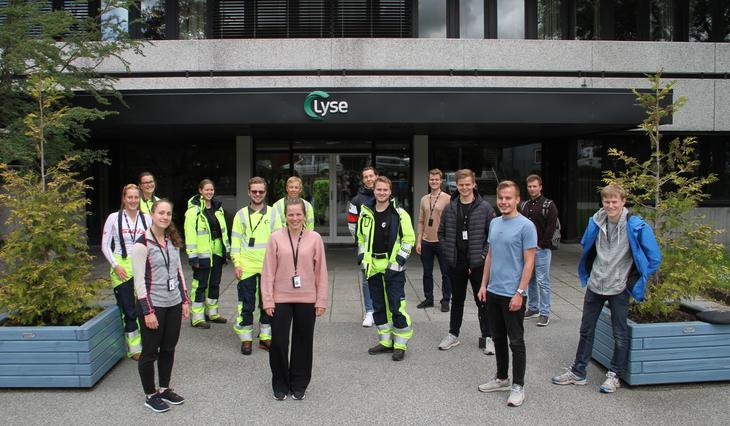 14 sommerstudenter samlet med behørig avstand utenfor hovedinngangen til Lyse Elnett med grønne busker på hver side