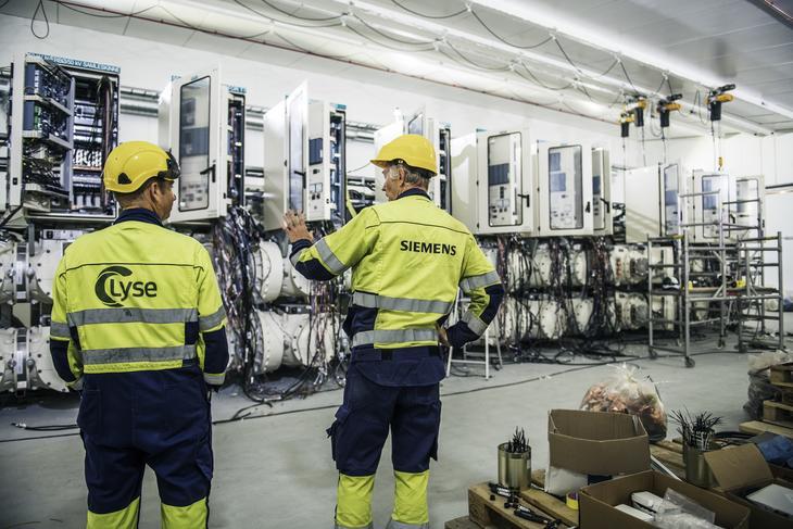 To ansatte i gule synlighetsklær står foran elektrisk anlegg som nå kobles til i nye Opstad transformatorstasjon