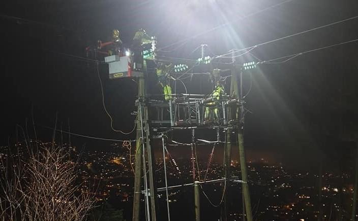Fire ansatte jobber om natten oppe i og ved en mast som er opplyst av lys fra drone. Bak er det lys fra boliger.